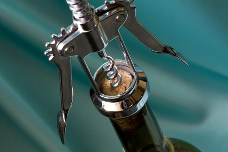 Close shot of a corkscrew opening a bottle of wine  Shallow dof photo