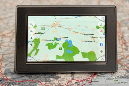 Portable GPS for a car sitting on a map photo
