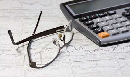 financial newspaper: A calculator, glasses, and financial statement  Selective focus