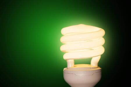 Energy saving light bulb on a green background  photo