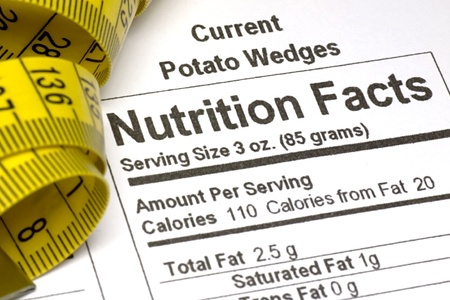 Yellow tape measure next to nutrition information on packaging in the USA photo