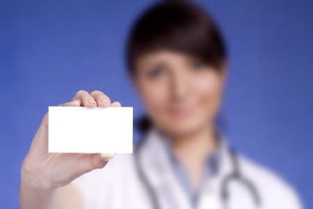 Women Doctor holding blank business card  Focus on fingers and card  photo