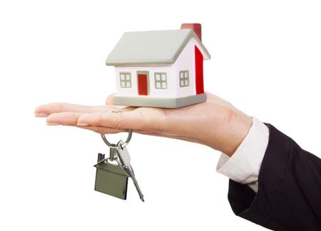 home for sale: Modello di casa in miniatura e le chiavi che poggia su una mano femminile