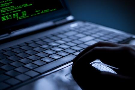 identity thieves: Hacker usando muchos port�tiles de d�gitos en la pantalla del ordenador
