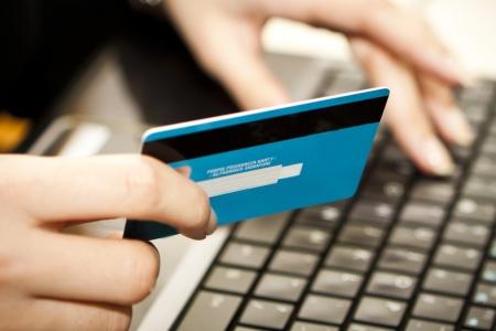tarjeta de credito: Manos de introducir la informaci�n de tarjetas de cr�dito en un ordenador port�til Foto de archivo