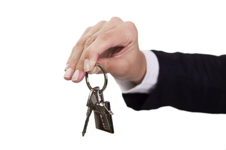 Woman holding out house keys on a silver house-shaped keychain photo