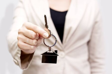 key ring: Woman holding out house keys on a silver house-shaped keychain
