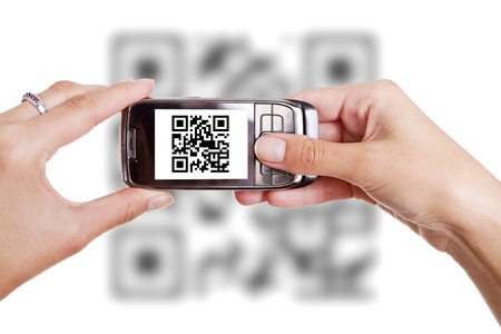 Human hands holding smart phone and scanning QR code photo