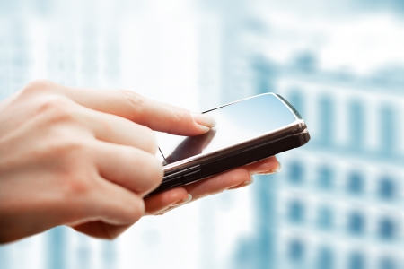 business technology: Closeup of female hands using a smart phone  City background