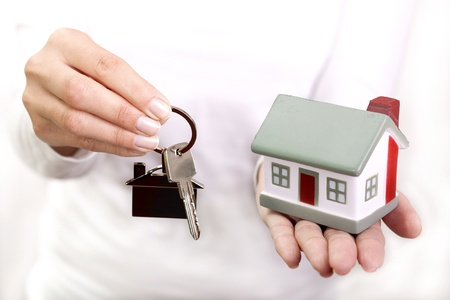 Miniature model house and keys resting on a female hand photo