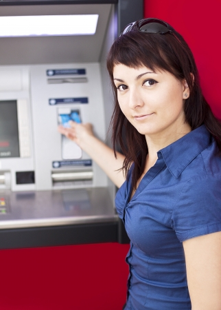 Beautiful woman using credit card, she is withdrawing money from an ATM machine  Stock Photo - 15378732