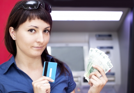 withdrawing: Beautiful woman using credit card, she is withdrawing money from an ATM machine