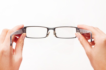 look through window: Hands holding eyeglasses on white background  Stock Photo