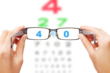 opthalmology: Human hands holding eyeglasses with eye chart in the back
