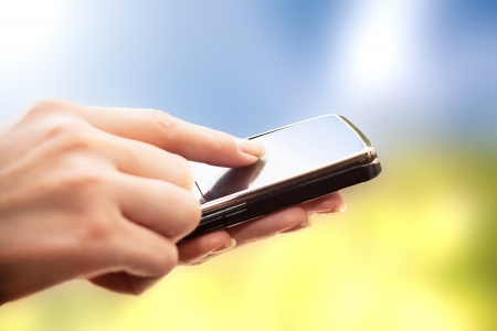 holding phone: Closeup of female hands using a smart phone  Nature background  Stock Photo