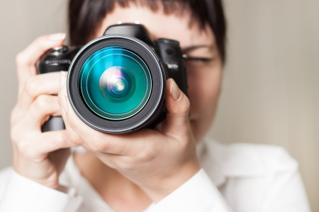 photography themes: Pretty woman is a professional photographer with dslr camera Stock Photo