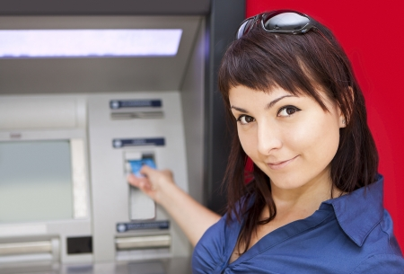 Beautiful woman using credit card, she is withdrawing money from an ATM machine  Stock Photo - 15605121