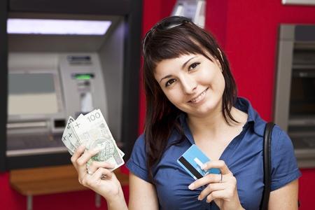 Mooie vrouw met behulp van een creditcard, is ze geld opnemen uit een geldautomaat