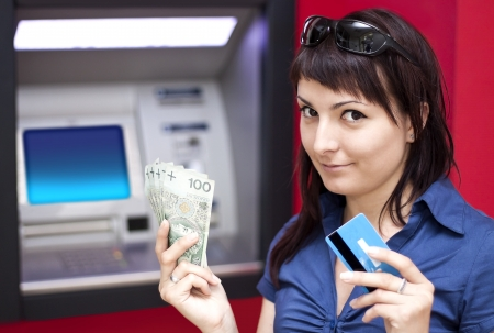 Beautiful woman using credit card, she is withdrawing money from an ATM machine  Stock Photo - 16405310