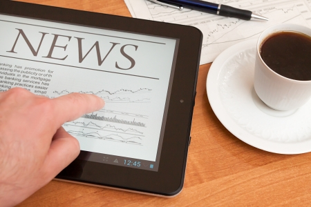 financial newspaper: Tablet PC shows latest news on screen, which lying on work place   Stock Photo