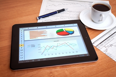 Desktop in stock exchange office with a tablet pc showing stock market chart   photo