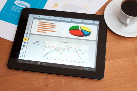 Desktop in stock exchange office with a tablet pc showing stock market chart Stock Photo - 17613391