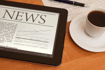 latest: Tablet PC shows latest news on screen, which lying on work place   Stock Photo