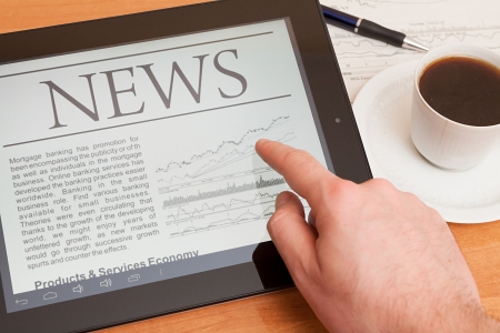 Tablet PC shows latest news on screen, which lying on work place Stock Photo - 18011770