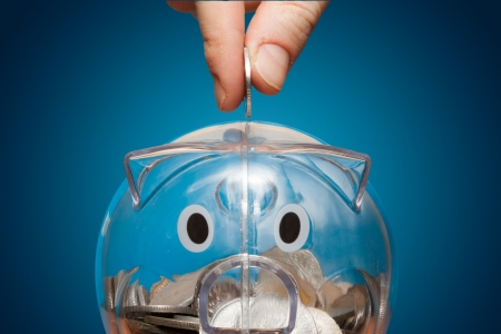bank crisis: Saving, male hand putting a coin into piggy bank