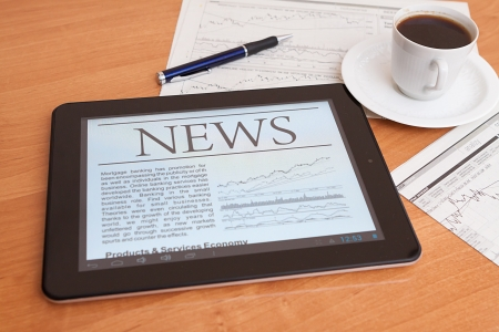 latest news: Tablet PC shows latest news on screen, which lying on work place   Stock Photo