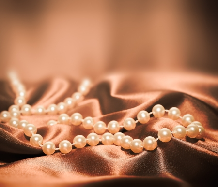 Pearls a necklace on a silk fabric photo