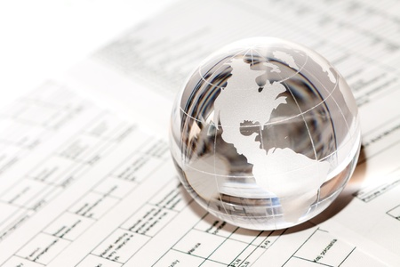 financial globe: Glass globe with North America and business papers