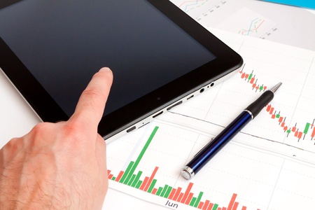 Desktop in stock exchange office with a tablet pc showing stock market chart Stock Photo - 18732830