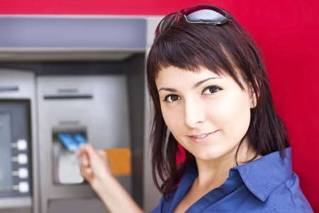 Beautiful woman using credit card, she is withdrawing money from an ATM machine Stock Photo - 19340026