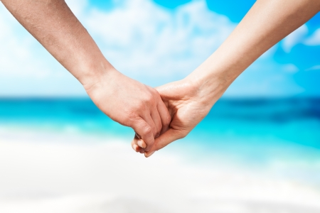 woman beach dress: Holding hands couple on beach  Romantic love and happiness Stock Photo