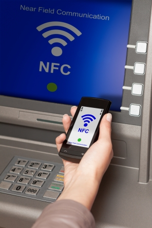 withdrawing money from atm with a mobile phone a NFC terminal Stock Photo - 19457778