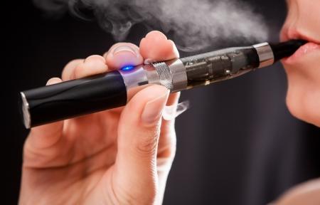 cigarette smoke: Primo piano di una donna che l'inalazione di una sigaretta elettronica