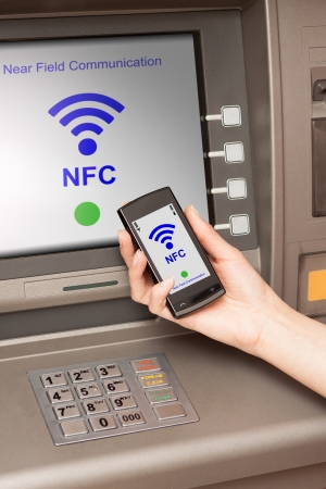 withdrawing money from atm with a mobile phone a NFC terminal Stock Photo - 20020507