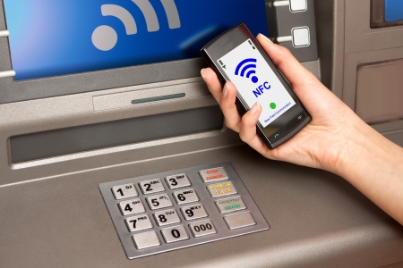 withdrawing money from atm with a mobile phone a NFC terminal Stock Photo - 20020516