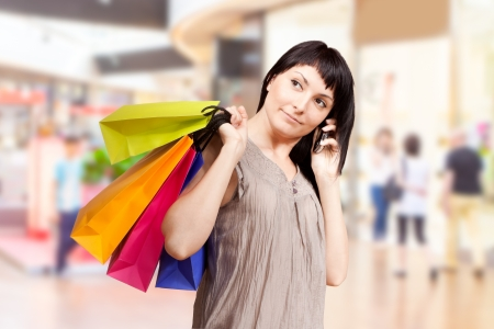 Smiling girl with shopping bags in shop Stock Photo - 20020504