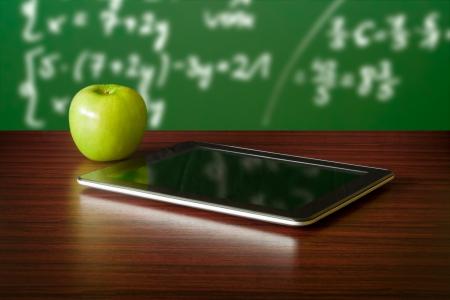 old technology: Tavoletta digitale e mela sulla scrivania di fronte alla lavagna
