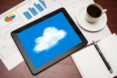 Modern workplace with digital tablet showing cloud photo