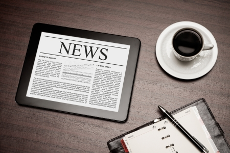 crisis economica: Tablet PC muestra las ?ltimas noticias en la pantalla, que miente en el lugar de trabajo