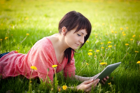 on pasture: Young woman using tablet outdoor laying on grass