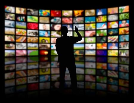 大きな TV パネルを見て若い男の背面図 写真素材