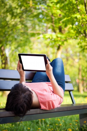 bench: Young woman using tablet outdoor laying on grass