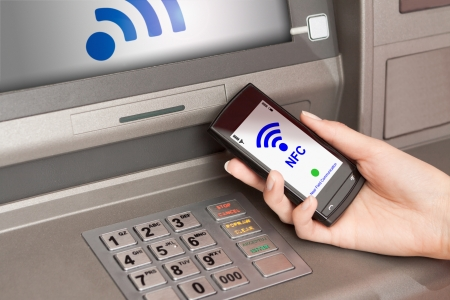 withdrawing money from atm with a mobile phone a NFC terminal Stock Photo - 21549823