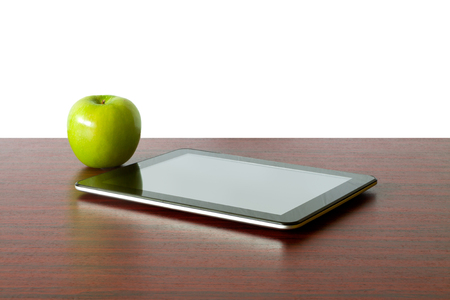 Digital tablet and apple on the desk in front of blackboard Stock Photo - 22268424