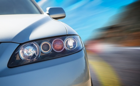 lights on: A car driving on a motorway at high speeds, overtaking other cars Stock Photo