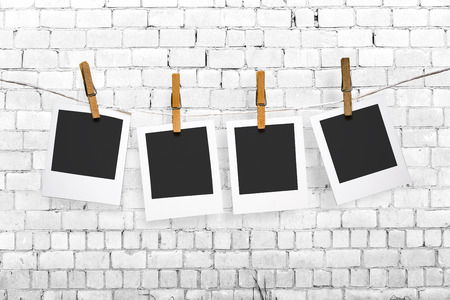 Blank photos hanging on a clothesline over brick wall background with copy space photo